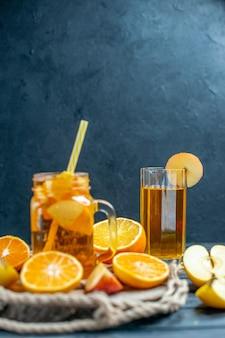 전면 보기 칵테일은 어두운 격리된 배경에 있는 나무 판자에 오렌지와 사과를 자른다