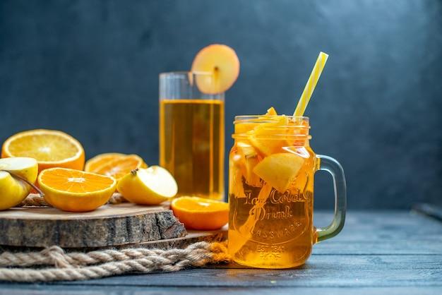 전면 보기 칵테일은 어두운 나무 판자에 오렌지와 사과를 자른다