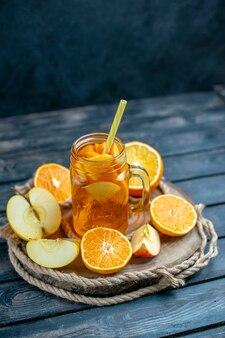 正面図カクテルカットオレンジとリンゴの木板に暗い