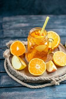 Вид спереди нарезанные апельсинами и яблоками на деревянной доске на темном фоне