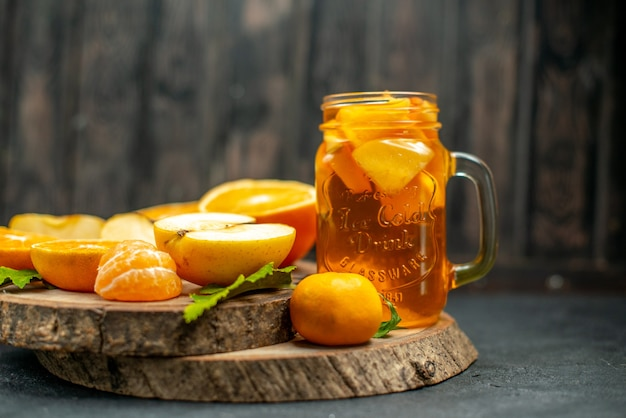 Vista frontale arance tagliate cocktail mele su oscurità