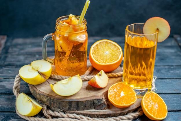 Vista frontale arance e mele tagliate cocktail su tavola di legno su oscurità