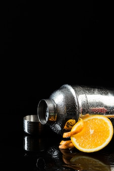 Front view of cocktail shaker with orange and copy space
