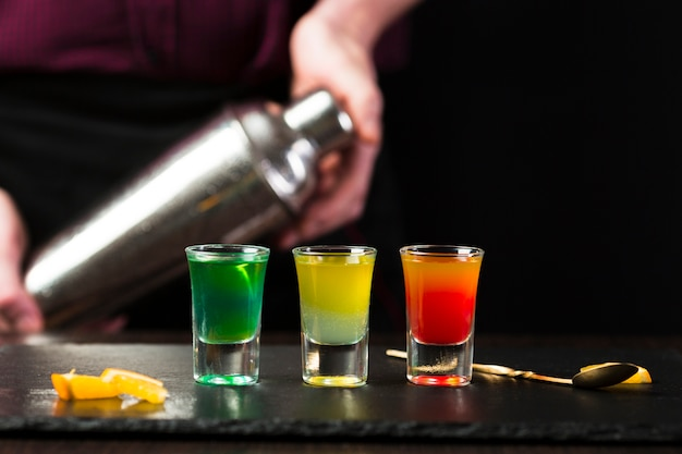 Front view of cocktail shots with defocused men