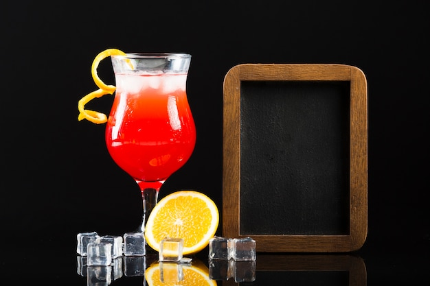 Front view of cocktail with ice cubes and blackboard