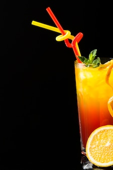 Front view of cocktails with straws and orange