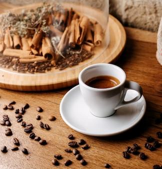 Передний вид кофе вместе с корицей и кофейными семечками вокруг на коричневом деревянном полу