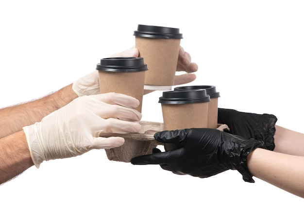 A front view coffee cups being delivered from female to male both in gloves