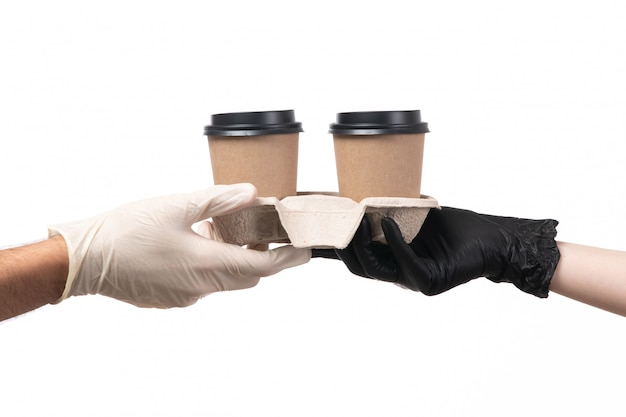 A front view coffee cups being delivered from female to male