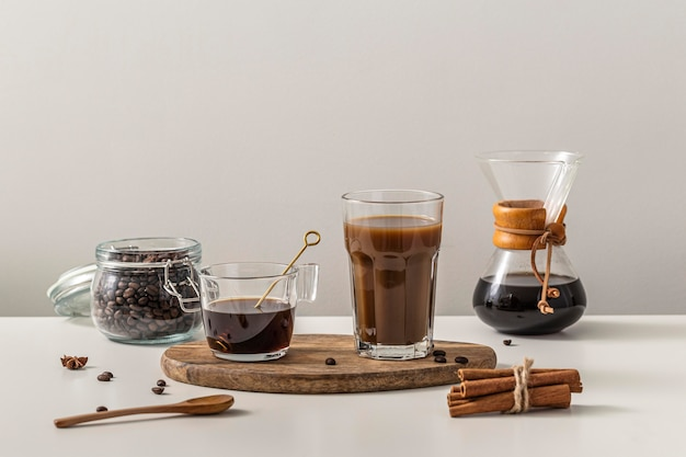Front view of coffee in different containers and cinnamon sticks
