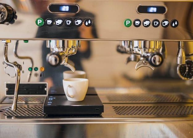 Vista frontale della macchina per il caffè con la tazza