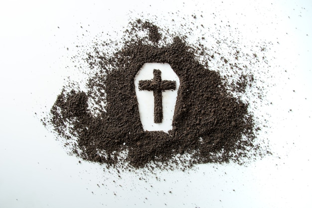 Front view of coffin shape with brown soil on white desk funeral death