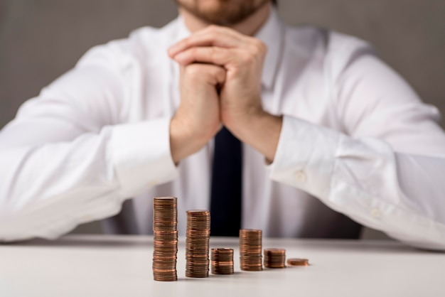 Front view of coins in front of businessman