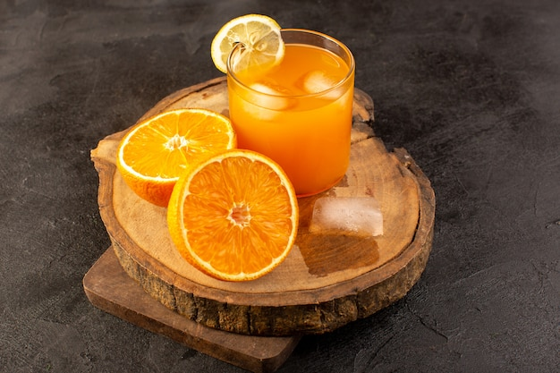 A front view cold cocktail colored inside glass with ice cubes oranges isolated on the dark