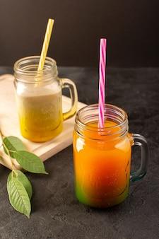 Una vista frontale cocktail freddi colorati all'interno di lattine di vetro con cannucce colorate foglie verdi sulla scrivania in legno crema e scuro