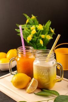 Una vista frontale cocktail freddi colorati all'interno di lattine di vetro con cannucce colorate limoni foglie verdi fiori sulla scrivania in legno crema e buio