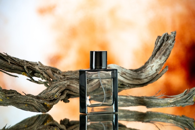 Front view cologne bottle branch rotten wood on nude background