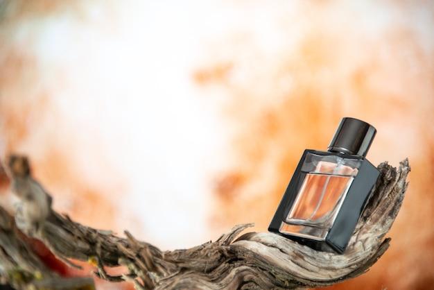 Vista frontale bottiglia di colonia su legno marcio ramo su sfondo nudo
