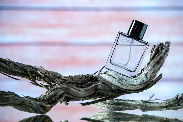 Front view of cologne bottle on rotten tree branch on beige wooden background