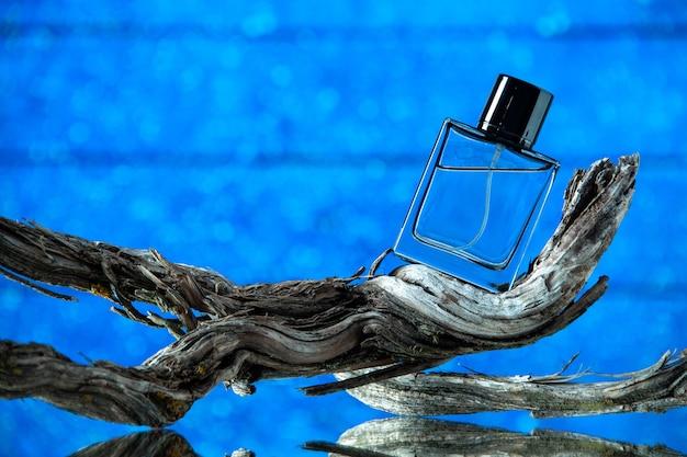 Vista frontale della bottiglia di colonia sul ramo di un albero marcio su sfondo blu copia posto