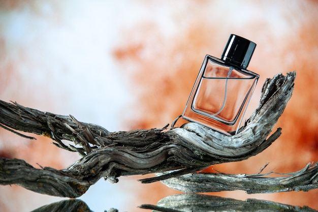 Front view of cologne bottle on rotten tree branch on blurred beige background