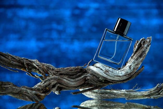 Bottiglia di colonia vista frontale sul ramo di un albero marcio su sfondo blu scuro