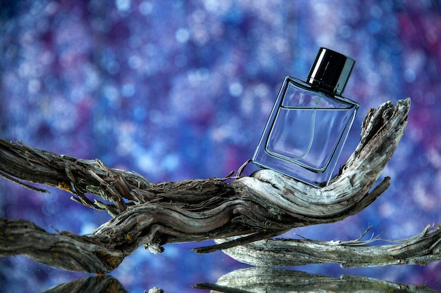 Front view of cologne bottle on rotten tree branch isolated on blurred purple background
