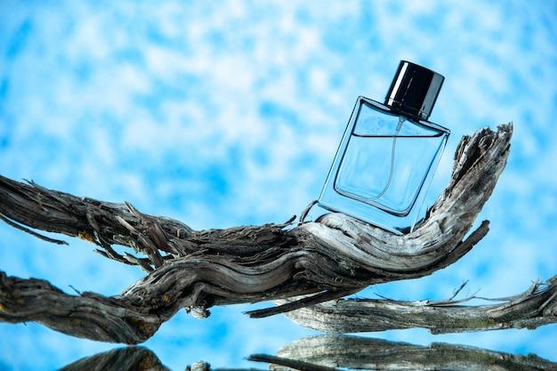 Bottiglia di colonia di vista frontale sul ramo di albero marcio sul posto della copia del fondo azzurro