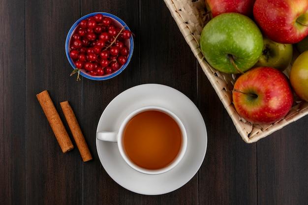 Vista frontale di mele colorate in un cesto con una tazza di tè alla cannella e ribes rosso su una superficie di legno