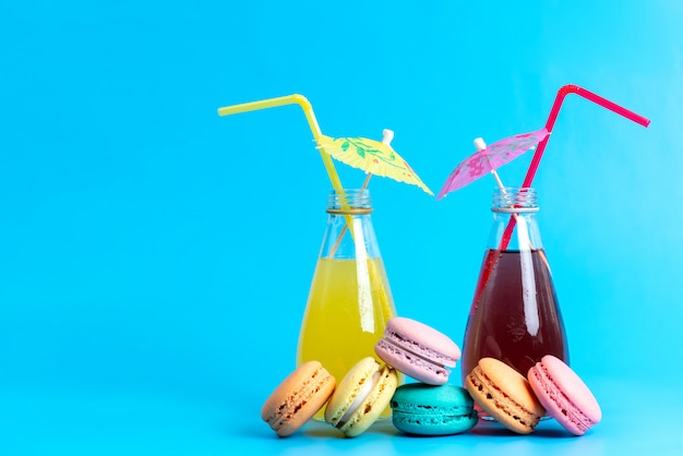A front view colored cocktails cooling with straws along with french macarons on blue