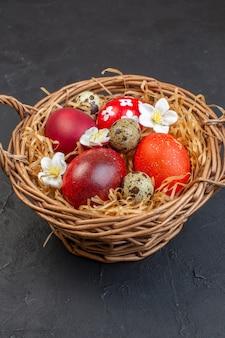 Вид спереди цветные пасхальные яйца внутри корзины на темной поверхности