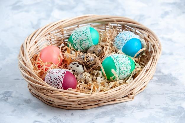 Вид спереди цветные пасхальные яйца внутри корзины белая поверхность