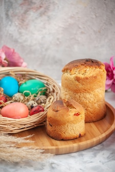 흰색 표면에 꽃과 케이크가 있는 바구니 안에 있는 색색의 부활절 달걀 전면 보기