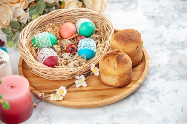 흰색 표면에 꽃과 촛불이 있는 바구니 안에 있는 색색의 부활절 달걀