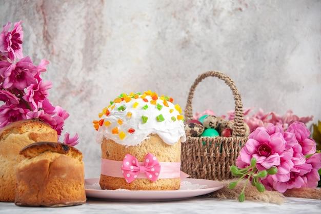 흰색 표면에 꽃과 케이크가 있는 디자인된 바구니 안에 있는 전면 보기 컬러 부활절 달걀