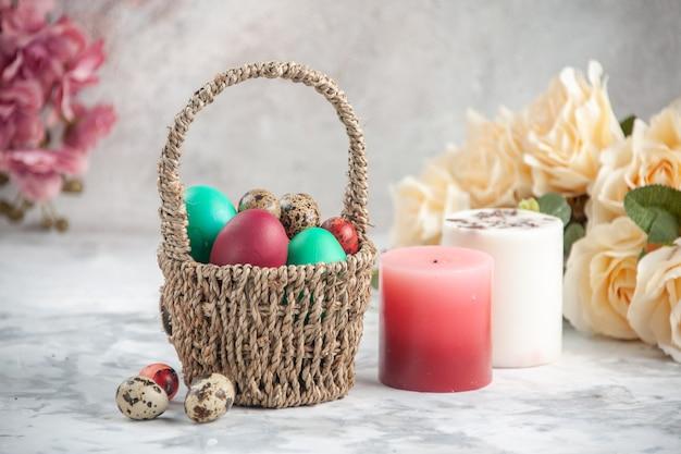흰색 표면에 꽃과 촛불이 있는 디자인된 바구니 안에 있는 전면 보기 컬러 부활절 달걀