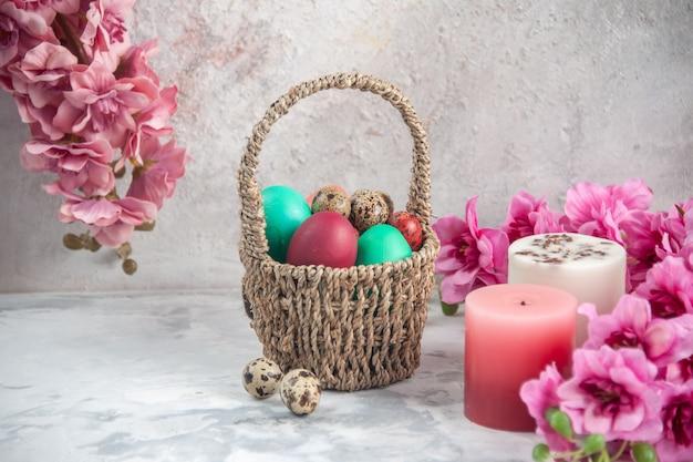 흰색 표면에 꽃이 있는 디자인된 바구니 안에 있는 전면 보기 컬러 부활절 달걀