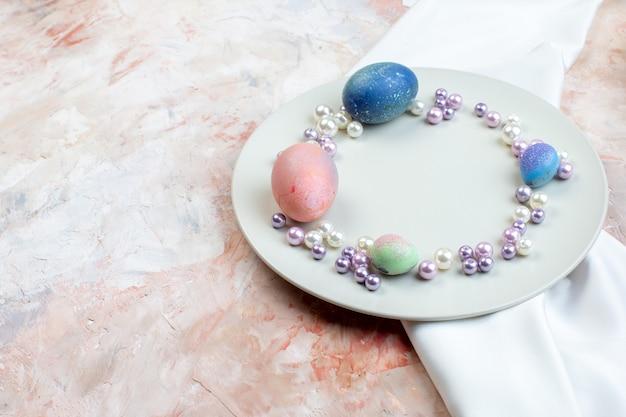 Вид спереди цветные пасхальные яйца внутри элегантной тарелки с бусами на светлом фоне концепция горизонтальные богато красочные весенние пасхальные праздники