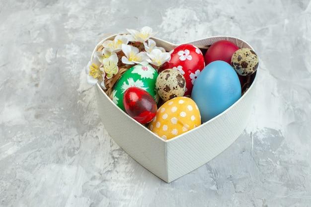 正面図白い背景の上のハート型のボックス内の着色されたイースターエッグイースター女性らしさの概念華やかなnovruzカラフルな春
