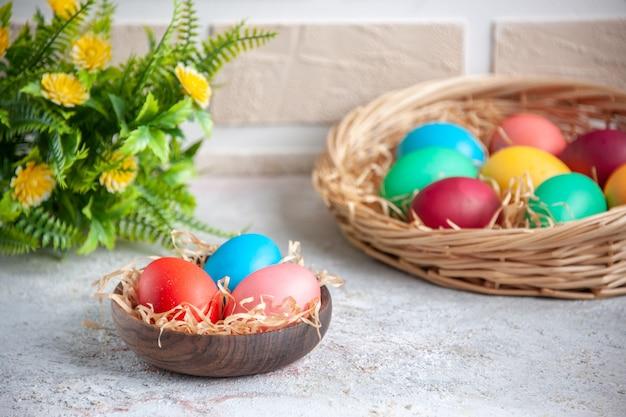 Вид спереди цветные пасхальные яйца внутри тарелки и корзины с цветами на белой поверхности витиеватых цветов красочная группа мульти весна