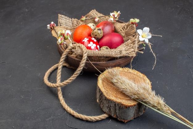 Вид спереди цветные пасхальные яйца внутри тарелки на темном фоне цвет праздник красочные концепция птица весна пасха богато украшенный