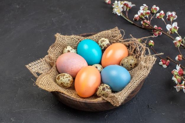 Вид спереди цветные пасхальные яйца внутри тарелки на темном фоне цвет праздник концепция птица весна богато красочные пасха