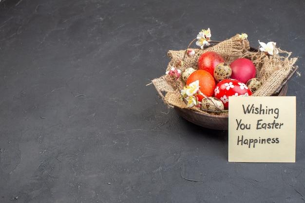 Вид спереди цветные пасхальные яйца внутри тарелки на темном фоне цвет праздник богато красочные концепция птица весна пасха