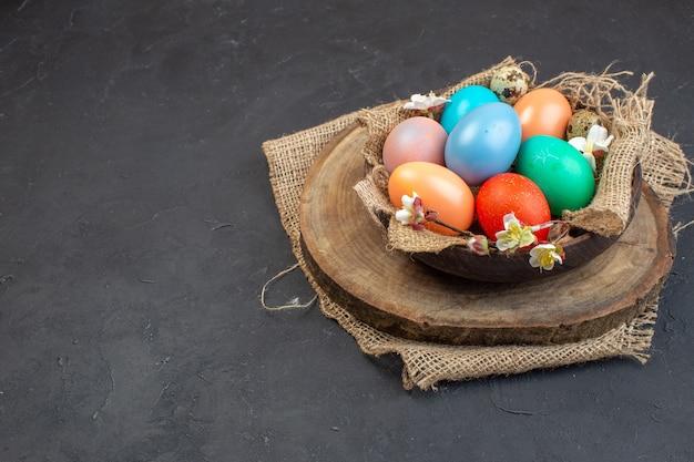 Вид спереди цветные пасхальные яйца внутри тарелки на темном фоне праздник красочные птицы пасхальный цвет весна богато украшенный