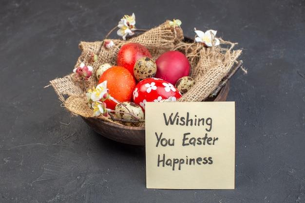 Вид спереди цветные пасхальные яйца внутри тарелки на темной поверхности цвет праздник богато красочные концепция птица весна пасха фото