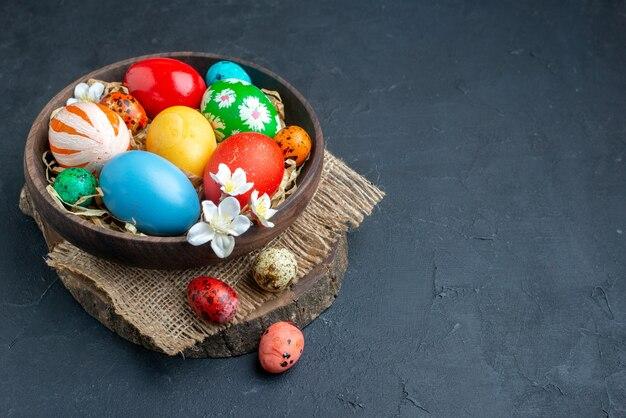 Вид спереди цветные пасхальные яйца внутри тарелки с соломой на темной поверхности богато украшенные красочные праздничные цвета мульти концепция весна