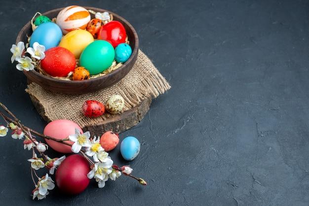 Вид спереди цветные пасхальные яйца внутри тарелки с соломой на темной поверхности богато украшенная красочная праздничная группа многоцветная концепция весна