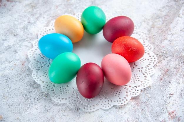 Вид спереди цветные пасхальные яйца на белом фоне группа разноцветных богато украшенных весенних цветов