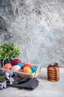 Вид спереди цветные пасхальные яйца с симпатичной коробкой на белой поверхности концепция группы многоэтнические цвета весна красочные богато