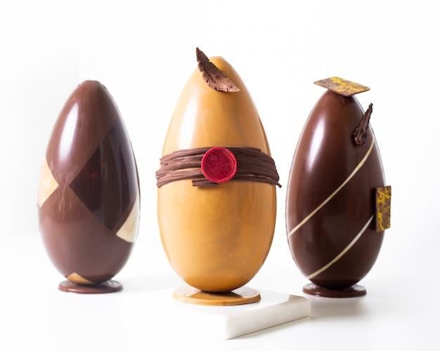 La vista frontale ha colorato le uova tre allineate il choco e le uova lunghe marroni sul pavimento bianco